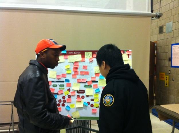 Community Ambassadors Abdi and Chong staff the program feedback station.